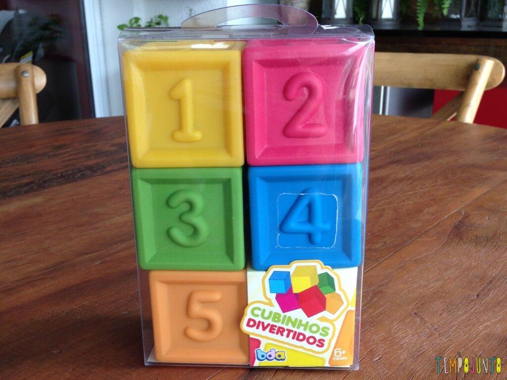E fica toda satisfeita com seu cubo laranja na boca - cubos de brinquedos
