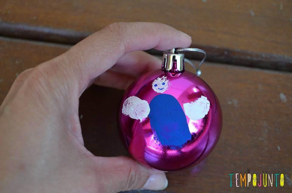 bola de natal rosa, com anjo feito de impressões digitais