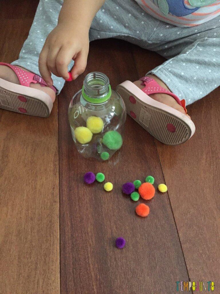 Como estimular o movimento de pinça do bebê - pompom no chão