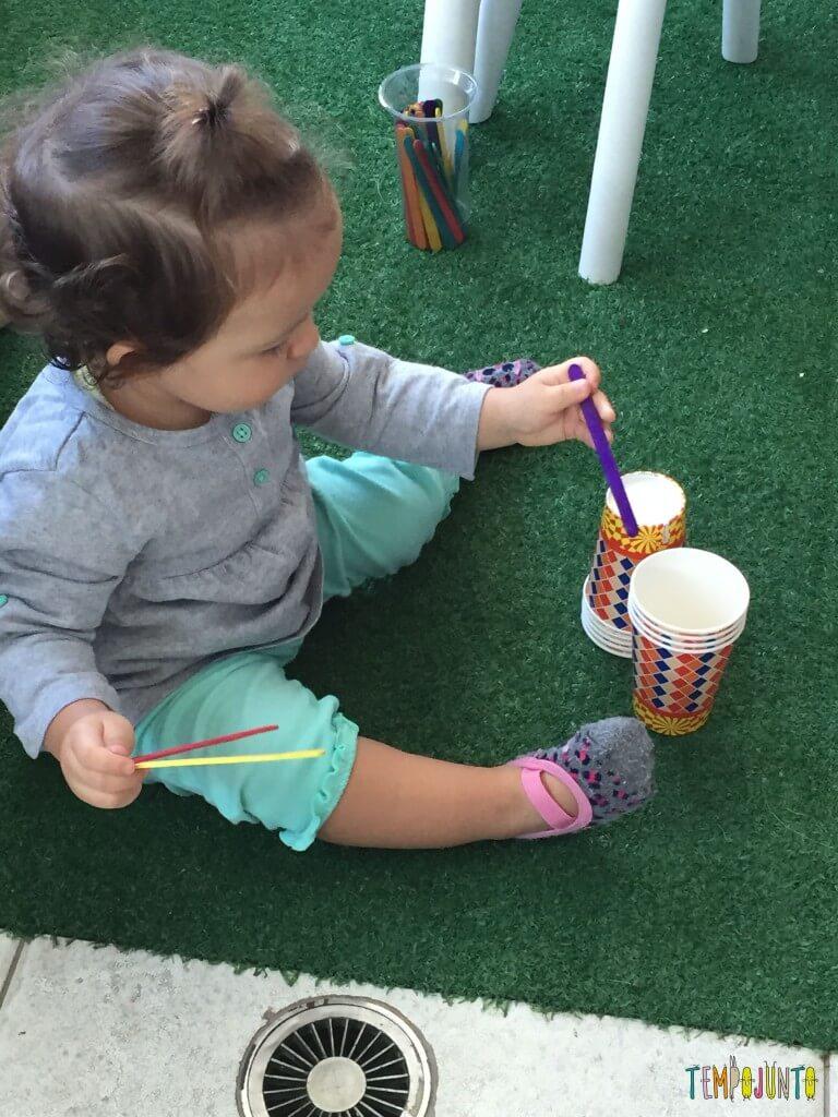 Brincadeira para bebês com copos descartáveis - guardando palito nos copos