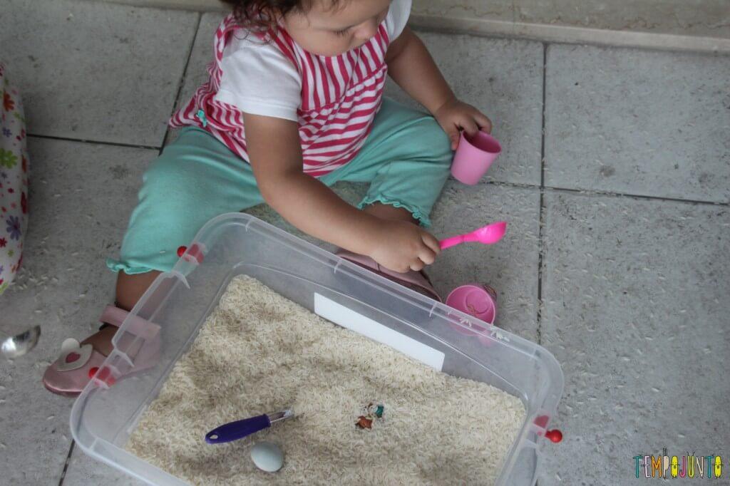 Brincadeira sensorial com arroz para bebês - jogando o arroz pra fora