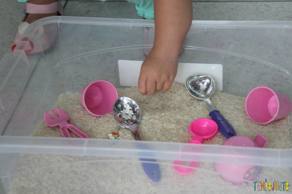 Brincadeira sensorial com arroz para bebês - manuseando o arroz com o dedinho