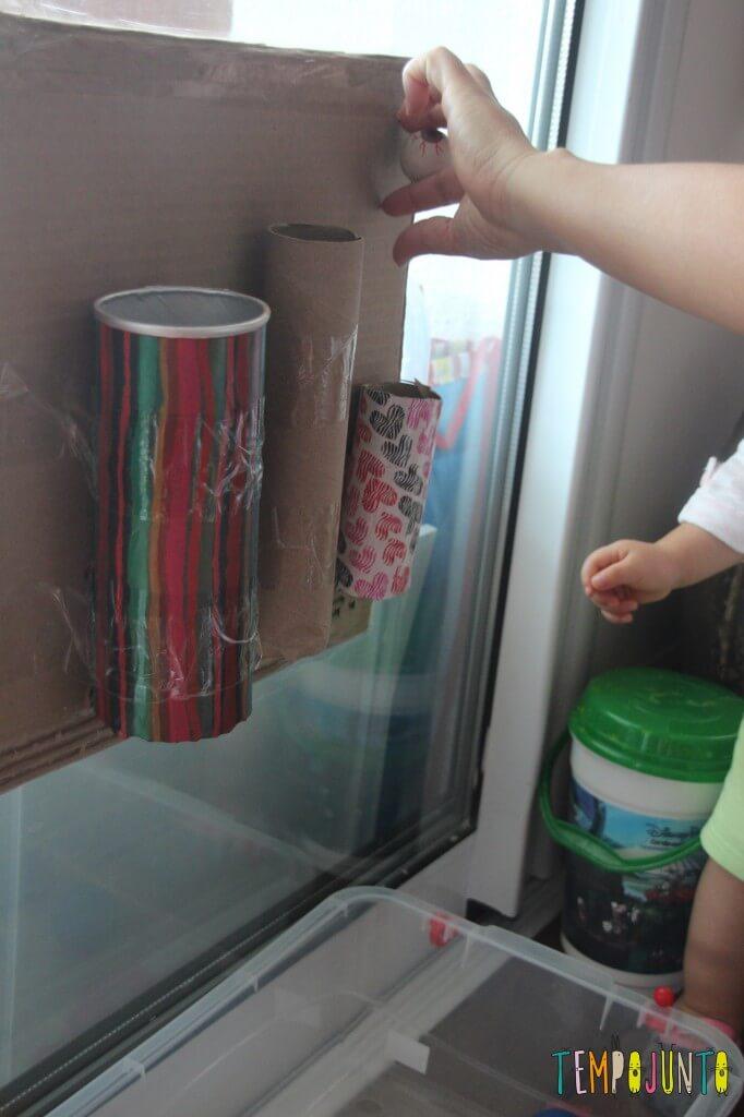 Brinquedo caseiro para bebês de 12 a 18 meses - colocando as bolas nos tubos