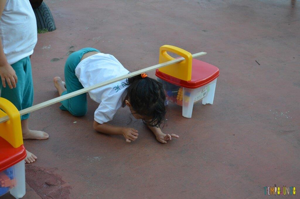 Brincadeira de circuito para as crianças - passando por debaixo do obstáculo
