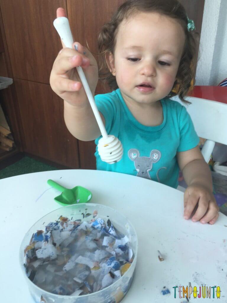 Brincadeira sensorial com papel picado - Gabi com o papel e a colher de mel