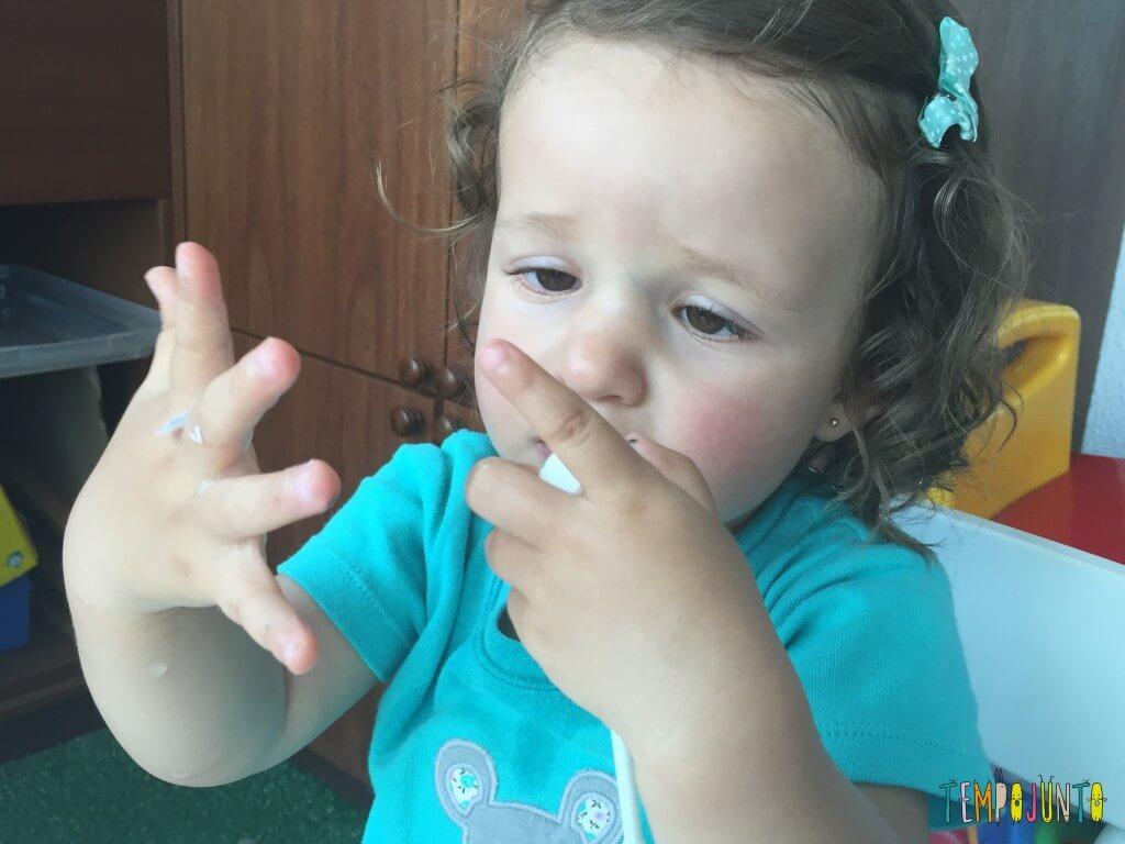 Brincadeira sensorial com papel picado - Gabi com o papel grudado na mao