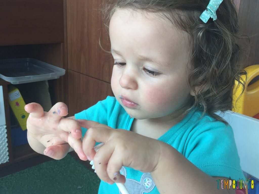 Brincadeira sensorial com papel picado - gabi descobre o papel grudado na mao