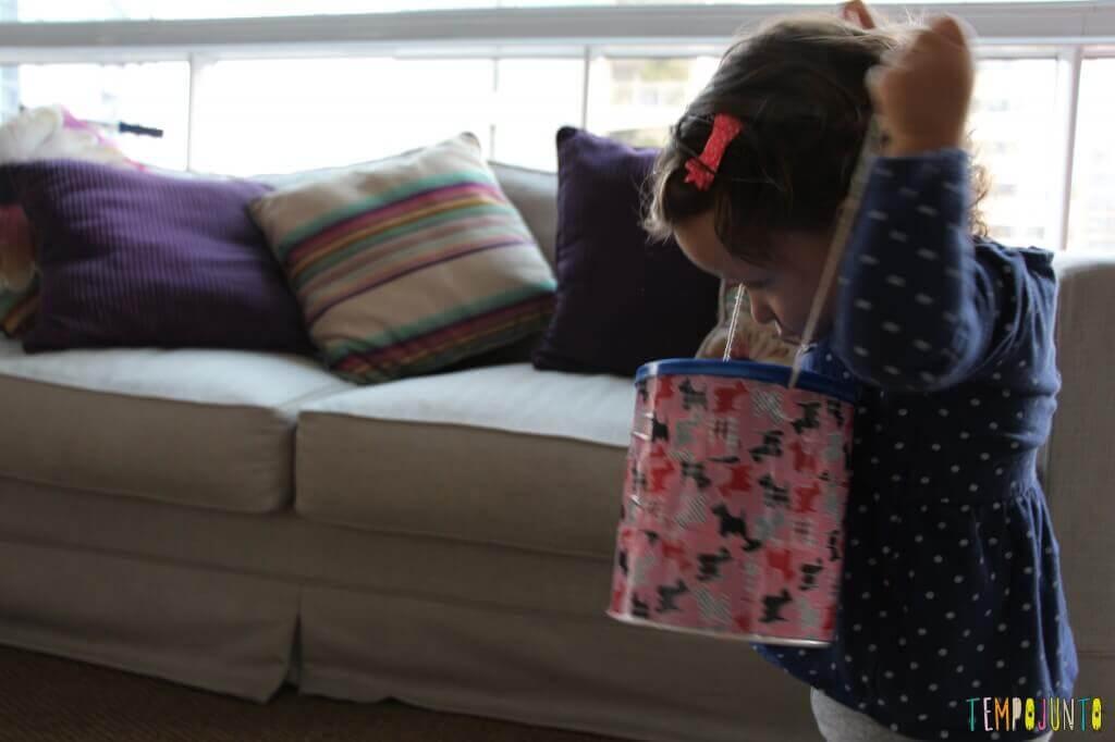 Como fazer um brinquedo para bebês com uma lata - Gabi colocando o tambor