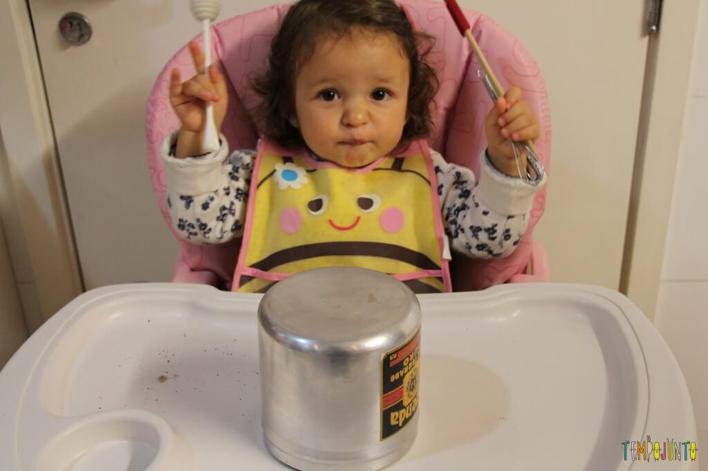 Mais um jeito de brincar com lata com os pequenos - gabi segurando os utensilios de cozinha