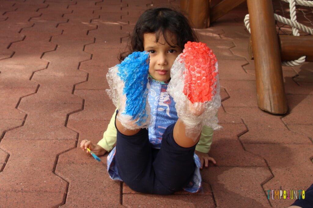 Pintura com plástico bolha nos pés pra divertir a garotada - Sofia com o pé pintado