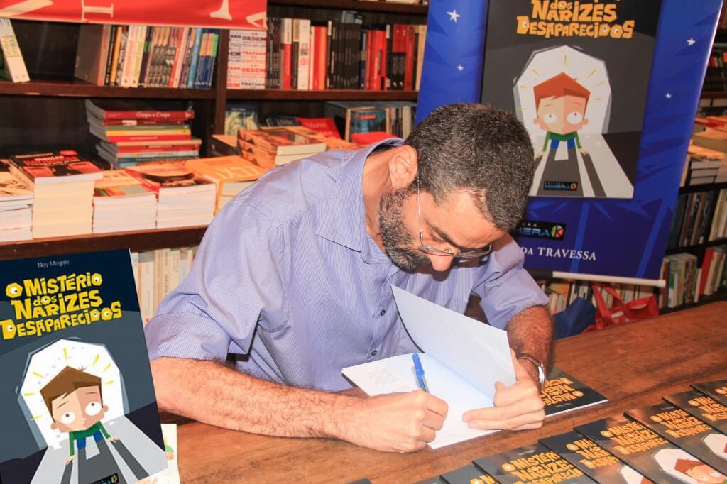 O arauto da alegria Ney Megale lança o Mistério dos Narizes Desaparecidos - Ney com o livro