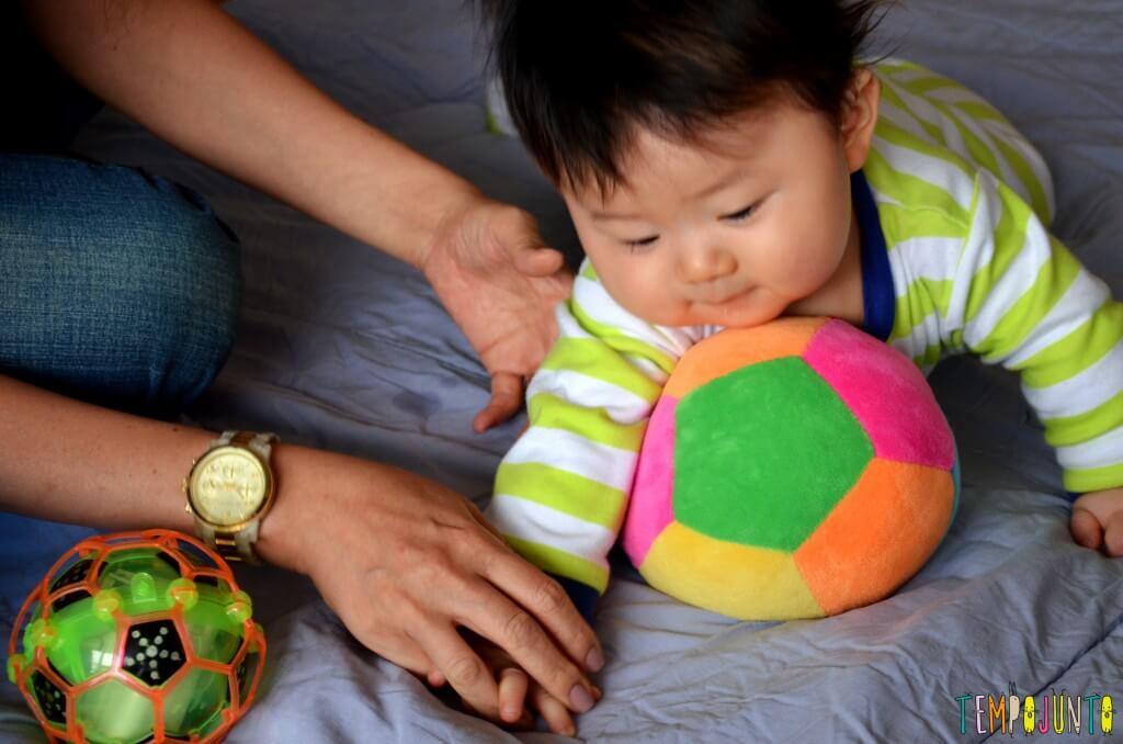 Como exercitar o bebê brincando com diferentes tipos de bolas - felipe deitando e rolando sobre a bola