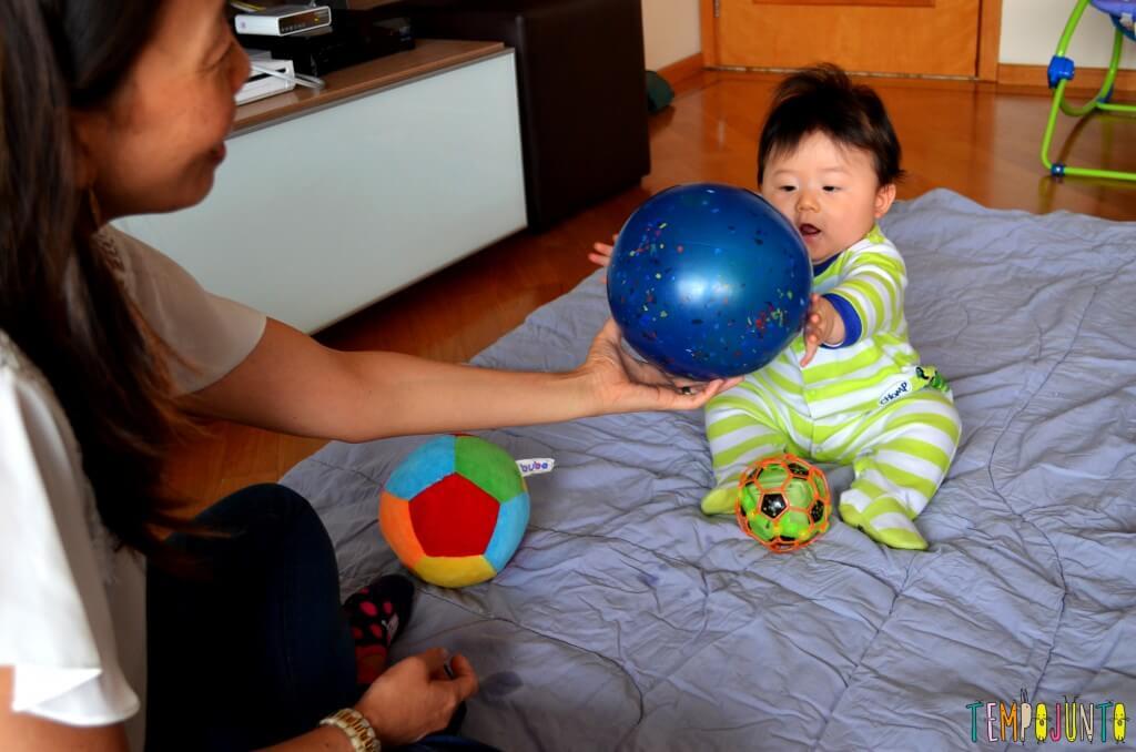 Como exercitar o bebê brincando com diferentes tipos de bolas - felipe pegando a bola de borracha