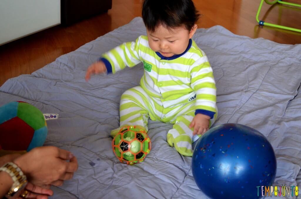 Como exercitar o bebê brincando com diferentes tipos de bolas - felipe sentado com as duas bolas