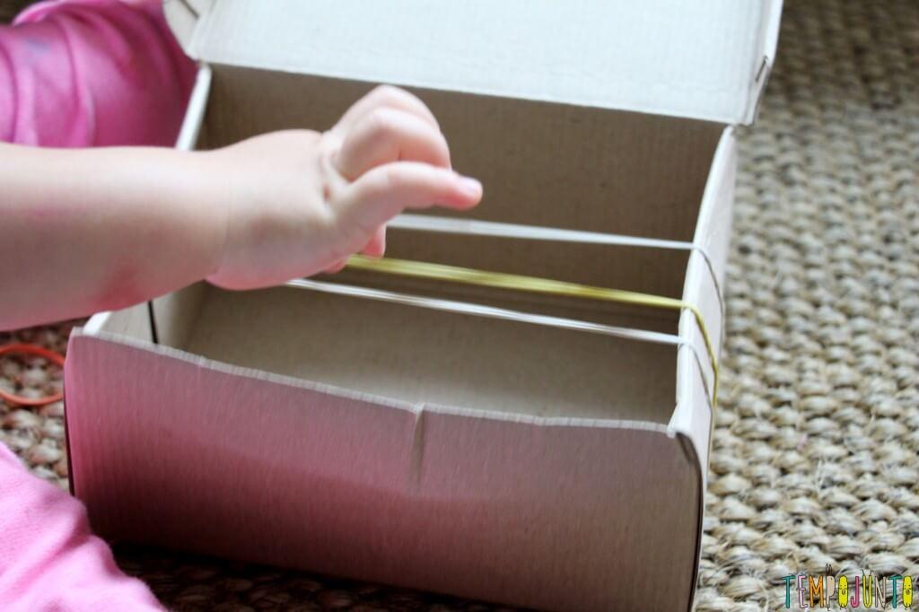 Como fazer um instrumento musical caseiro para os pequenos - gabi mexendo nos elasticos