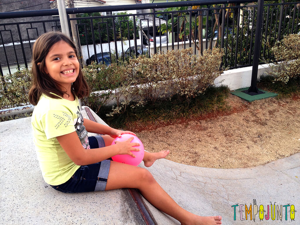 Uma bola uma rampa e a brincadeira ao ar livre está pronta - menina sentada na rampa com a bola