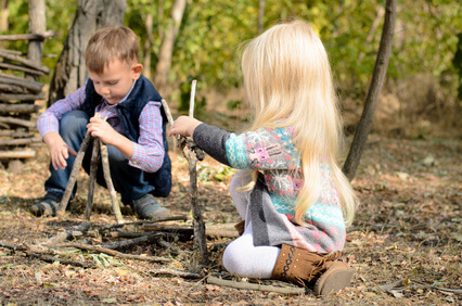 Little boy and girl playing in woods with sticks