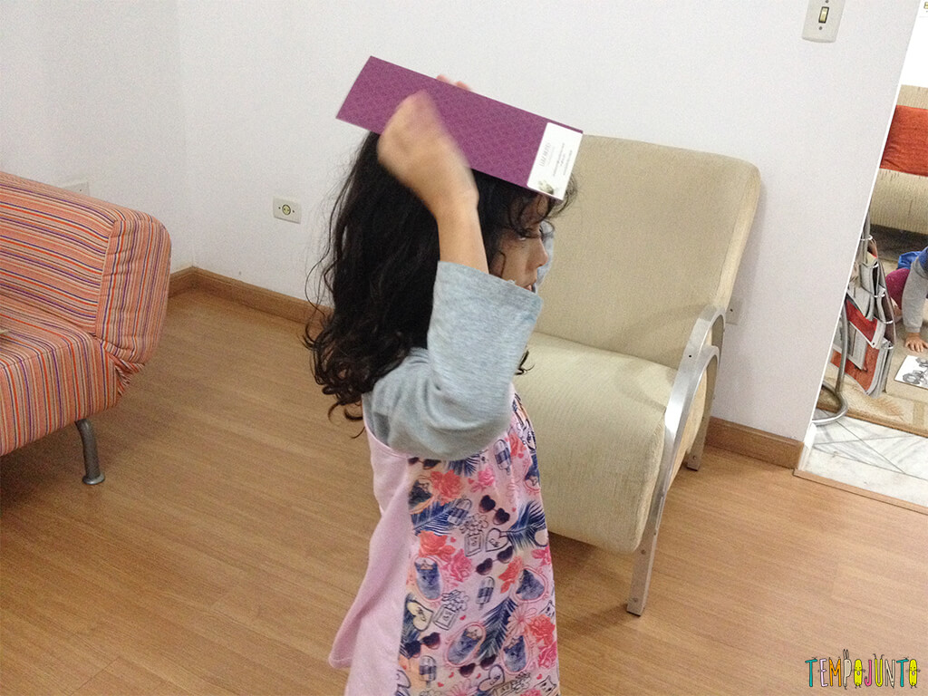 Brincadeira para quem tem 10 minutinhos com uma folha de guardanapo - sofia com o papel na cabeça