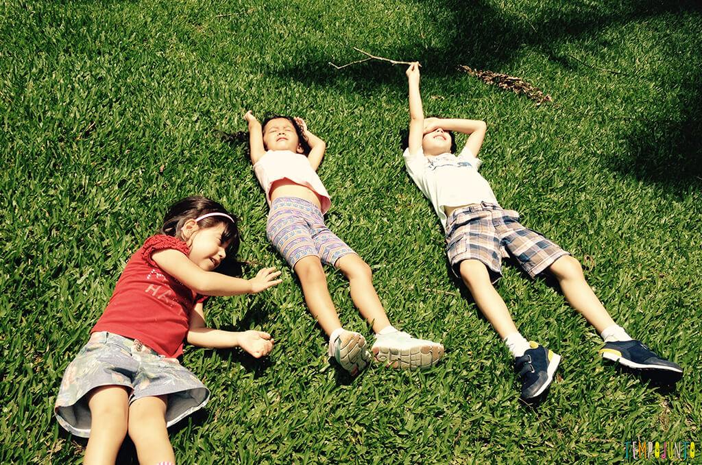 Brincar livre ao ar livre aproveitando o que as praças e parques têm disponível - criancas deitadas na grama