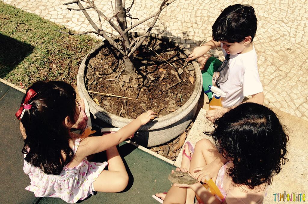 Brincar livre ao ar livre aproveitando o que as praças e parques têm disponível - criancas mexendo no vaso de terra