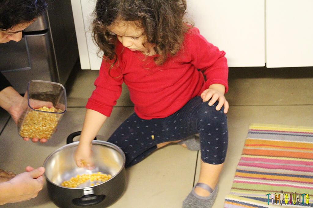Quando é a hora das crianças irem para a cozinha - gabi colocando a pipoca na panela