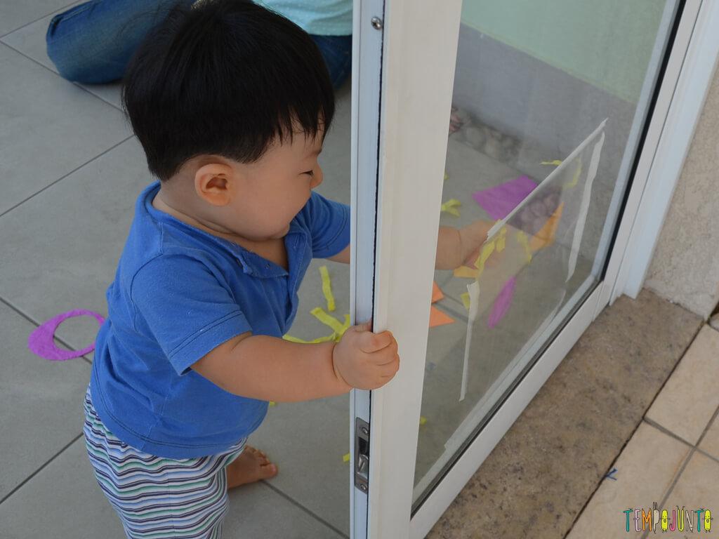 Brincadeira sensorial para seu bebe com papel de seda_11.37.47_Felipe encostando nos materiais2
