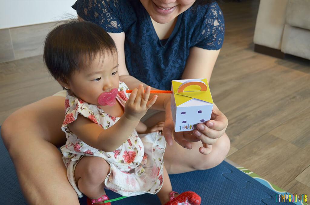 Jogo de encaixe para estimular a coordenação dos bebês - bebe concentrada com os puxadores