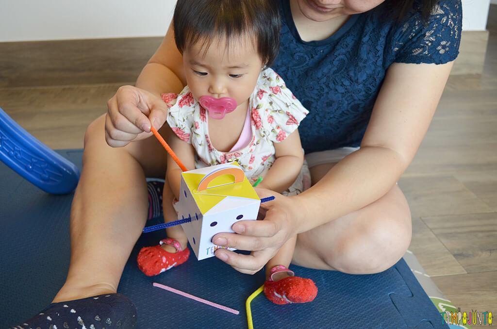 Jogo de encaixe para estimular a coordenação dos bebês - bebe olhando a mae encaixar os puxadores