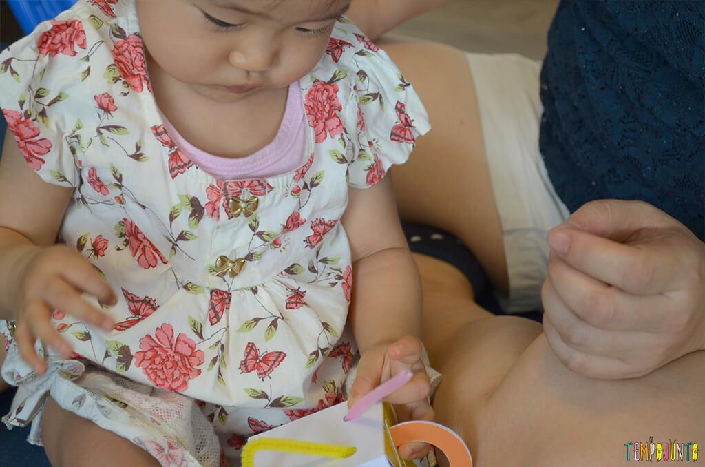 Jogo de encaixe para estimular a coordenação dos bebês - bebe olhando o brinquedo