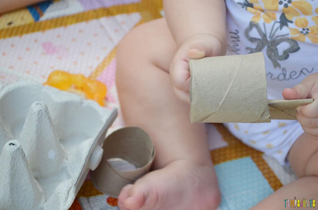 Brincadeira de coordenação com rolo de papel e caixa de ovos - luisa puxando o rolo pra fora