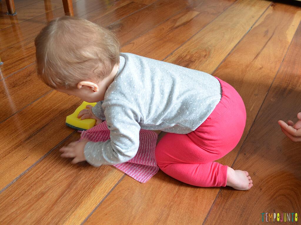 Brincadeira sensorial e de descoberta do bebê com material de cozinha_10.23.30_carolina-esfregando-a-esponja-no-chão