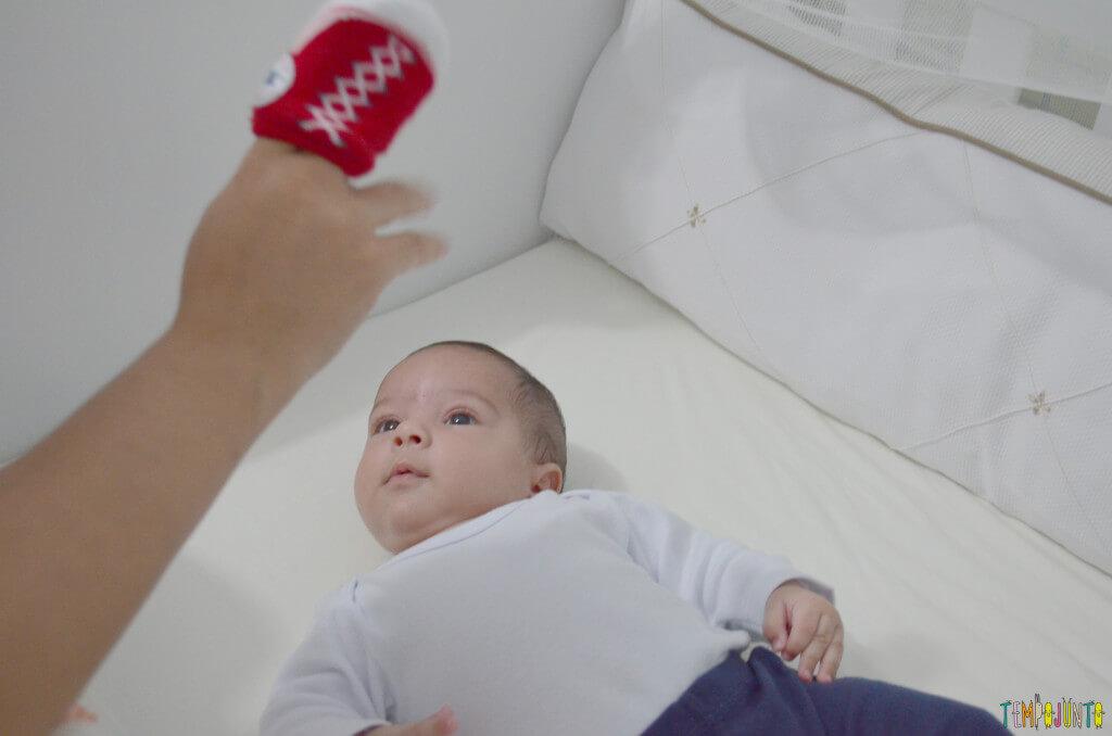 Usar suas mãos para brincar com o recém-nascido - bebe olhando o tenis