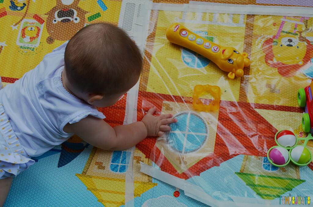 Brincadeira sensorial que ajuda o bebê a ficar de bruços - Luisa brincando com o tapete e os brinquedos