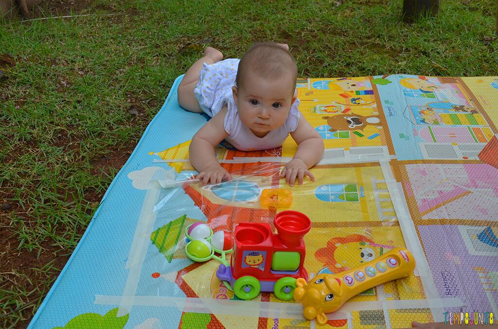 Brincadeira sensorial que ajuda o bebê a ficar de bruços - Luisa olhando para os brinquedos