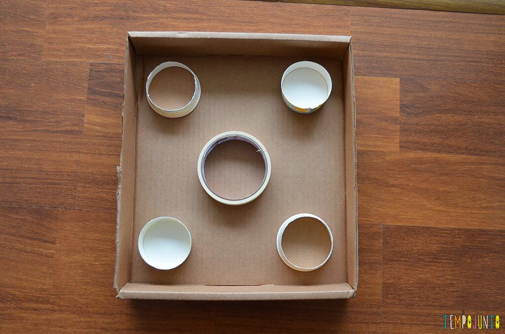 Um brinquedo para praticar a paciência e o sentido de direção - caixa com as bolinhas