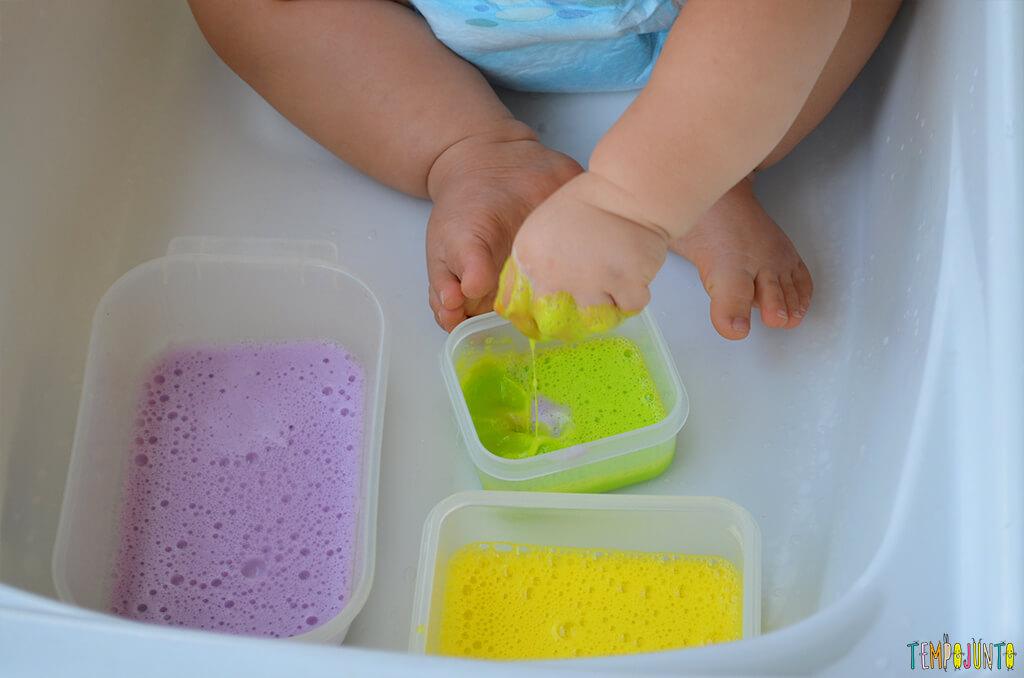 Brincadeira sensorial com espuma colorida para bebês - felipe molhando as maozinhas com a espuma