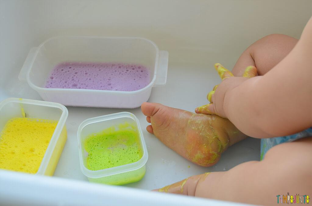 Brincadeira sensorial com espuma colorida para bebês - felipe molhando as perninhas com a espuma
