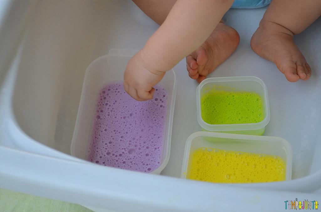 Brincadeira sensorial com espuma colorida para bebês - felipe pondo as maozinhas na espuma