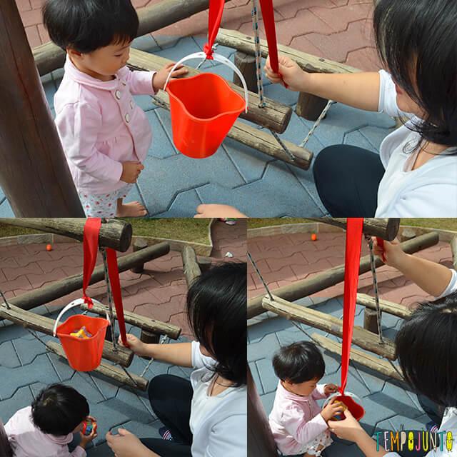Despertar a curiosidade do bebê com uma brincadeira de causa e efeito - bebe pegando os brinquedos do baldinho