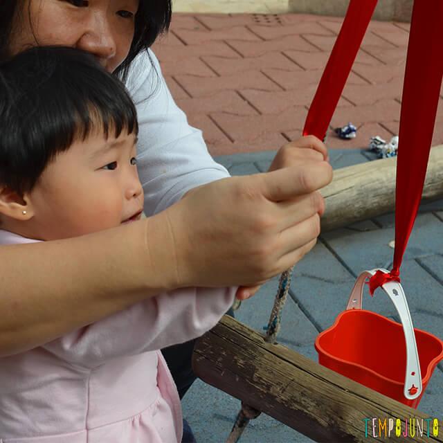 Despertar a curiosidade do bebê com uma brincadeira de causa e efeito - mae ajudando o bebe a brincar (IG)