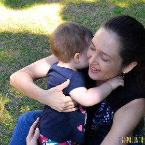 mãe abraça sua filha bebê no final de uma brincadeira