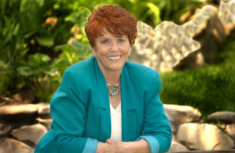 Na foto, close de Jane Nelsen, criadora da Disciplina Positiva, sorrindo, sentada, vestindo num terno azul